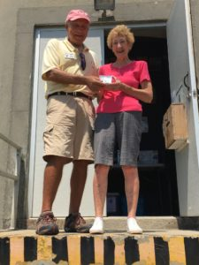 Jean D. receiving a complimentary OILH Xmas ornament from E. Gifford Stack FOIL board member and lighthouse tour coordinator after her successful climb as the most senior female climber
